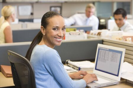 Businesswoman in cubicle using laptop smiling photo