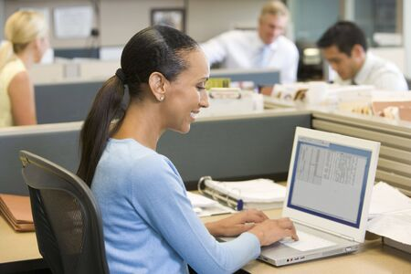 open plan office: Businesswoman in cubicle using laptop smiling