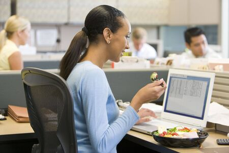 lunch break: Businesswoman in cubicle eating sushi smiling