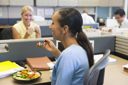 Businesswoman in cubicle eating salad and smiling photo