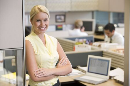 working week: Businesswoman standing in cubicle smiling
