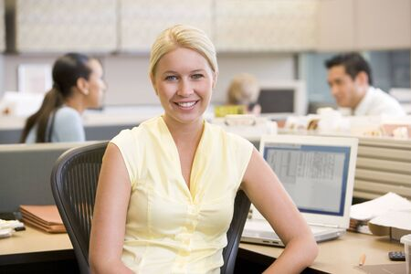 Businesswoman in cubicle smiling photo