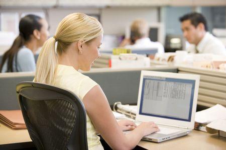 open plan office: Businesswoman in cubicle using laptop