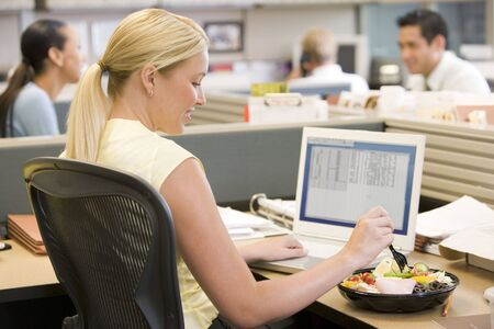 office break: Businesswoman in cubicle using laptop and eating salad