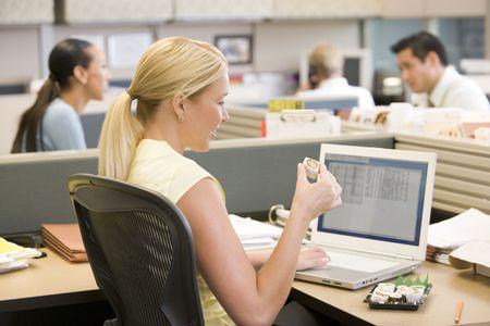 working week: Businesswoman in cubicle using laptop eating sushi