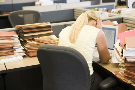 Businesswoman in cubicle with laptop and stacks of files photo