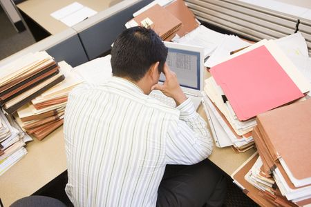 Businessman in cubicle with laptop and stacks of files Stock Photo - 3471627
