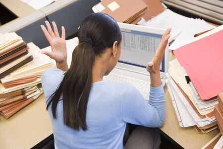 Businesswoman in cubicle with laptop and stacks of files Stock Photo - 3472466