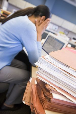 Businesswoman in cubicle with laptop and stacks of files Stock Photo - 3461059