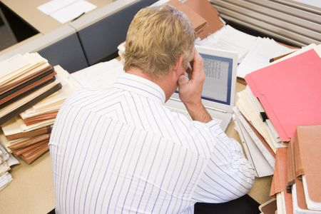 Businessman in cubicle with laptop and stacks of files photo