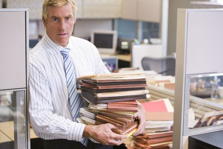 working week: Businessman standing in cubicle holding stacks of files