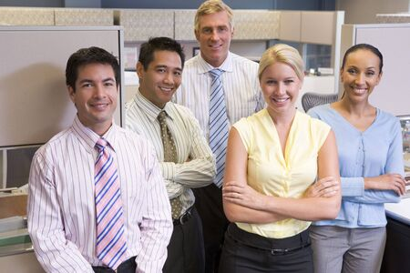 Business team standing in cubicle smiling photo