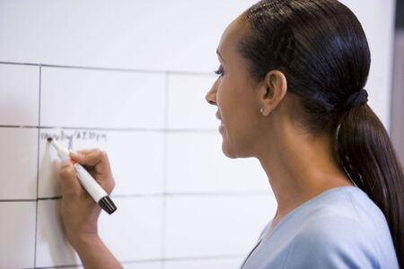dry erase: Businesswoman indoors writing on erasable board