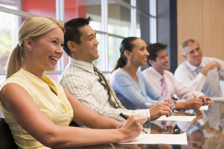 boardroom meeting: Five businesspeople at boardroom table smiling Stock Photo