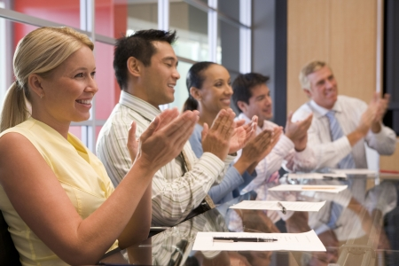 Five businesspeople at boardroom table applauding and smiling photo