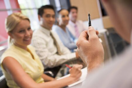 Five businesspeople at boardroom table with focus on businessmans pen photo