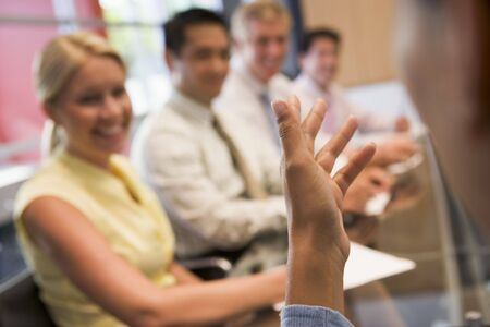 Five businesspeople at boardroom table with focus on businessmans hand photo