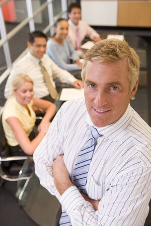 Businessman with four businesspeople at boardroom table in background photo