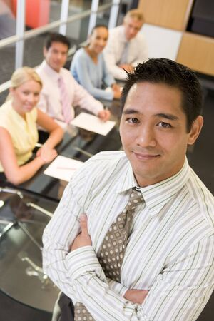 chinese american: Businessman with four businesspeople at boardroom table in background