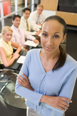 Businesswoman with four businesspeople at boardroom table in background photo