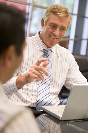 Two businessmen in boardroom with laptop talking photo