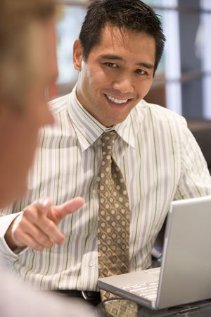 working week: Two businessmen in boardroom with laptop talking Stock Photo