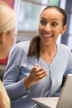 deux personnes qui parlent: Deux femmes d'affaires en salle de parler avec un ordinateur portable