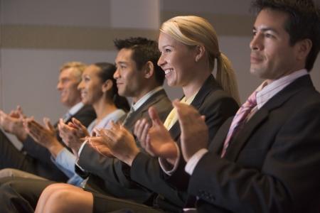 delegates: Cinque uomini d'affari e sorride applaudendo la presentazione in sala Archivio Fotografico