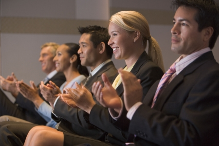 Five businesspeople applauding and smiling in presentation room Stock Photo - 3475273
