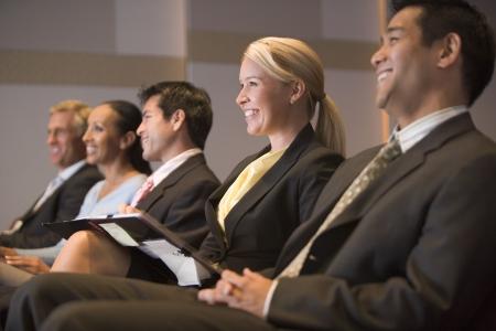 delegates: Cinque uomini d'affari sorridente nella presentazione camera con clipboards Archivio Fotografico