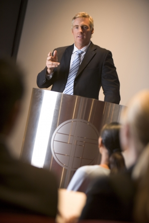 Businessman giving presentation at podium photo