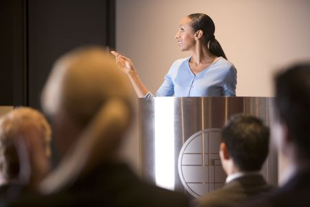 Businesswoman giving presentation at podium photo
