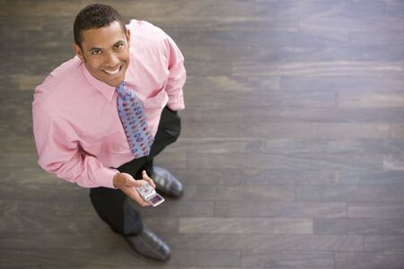 overhead view: Businessman standing indoors with cellular phone smiling