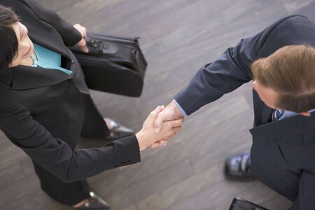 Two businesspeople standing indoors shaking hands photo