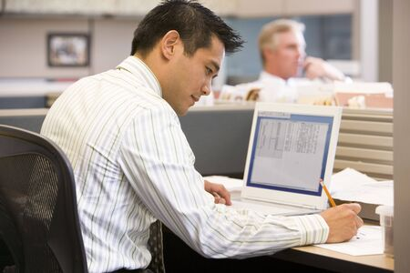 Businessman in cubicle with laptop writing photo