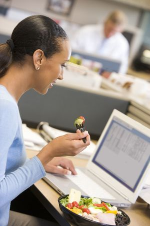 office cubicle: Businesswoman in cubicle with laptop eating salad Stock Photo