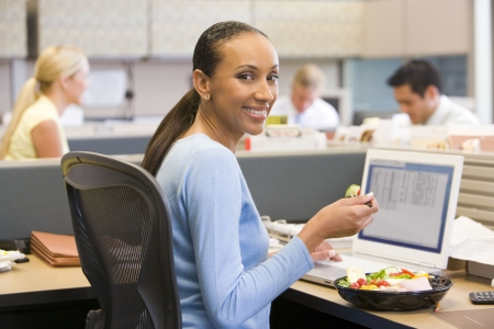 working week: Businesswoman in cubicle with laptop eating salad Stock Photo
