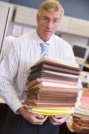 Businessman standing in cubicle with stacks of files photo