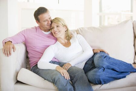 couple cuddling: Couple relaxing in living room and smiling Stock Photo