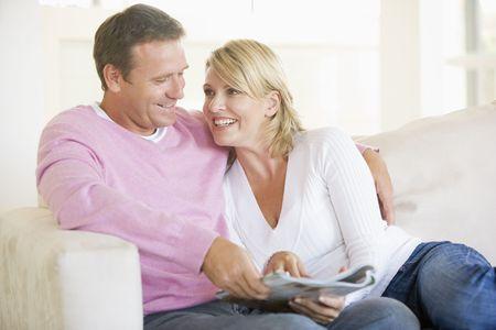 leggere rivista: Coppia di relax con una rivista e sorridente