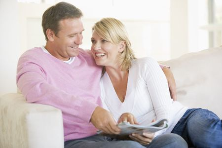 adult magazine: Couple relaxing with a magazine and smiling Stock Photo
