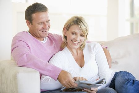 adult magazines: Couple relaxing with a magazine and smiling Stock Photo