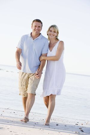parejas caminando: Pareja en la playa tomarse de las manos y sonriendo