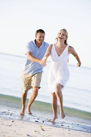 Couple at the beach playing and smiling photo