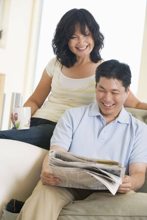 Couple relaxing with a newspaper and smiling photo