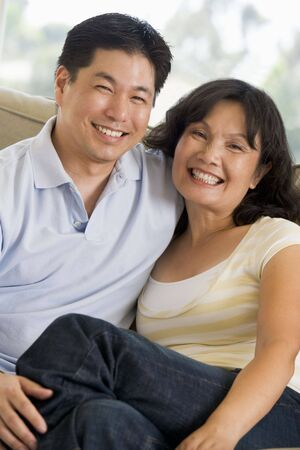 Couple relaxing in living room and smiling photo