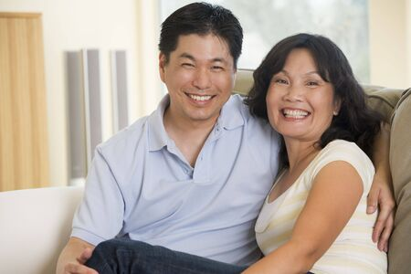 40s: Couple relaxing in living room and smiling Stock Photo