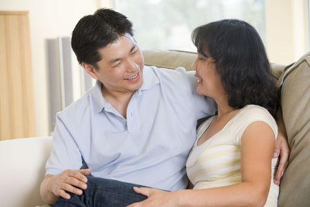 Couple relaxing in living room talking and smiling photo
