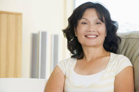 mujeres sentadas: Mujer sentada en la sala sonriendo