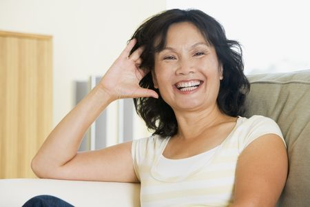 relaxed woman: Woman sitting in living room laughing Stock Photo
